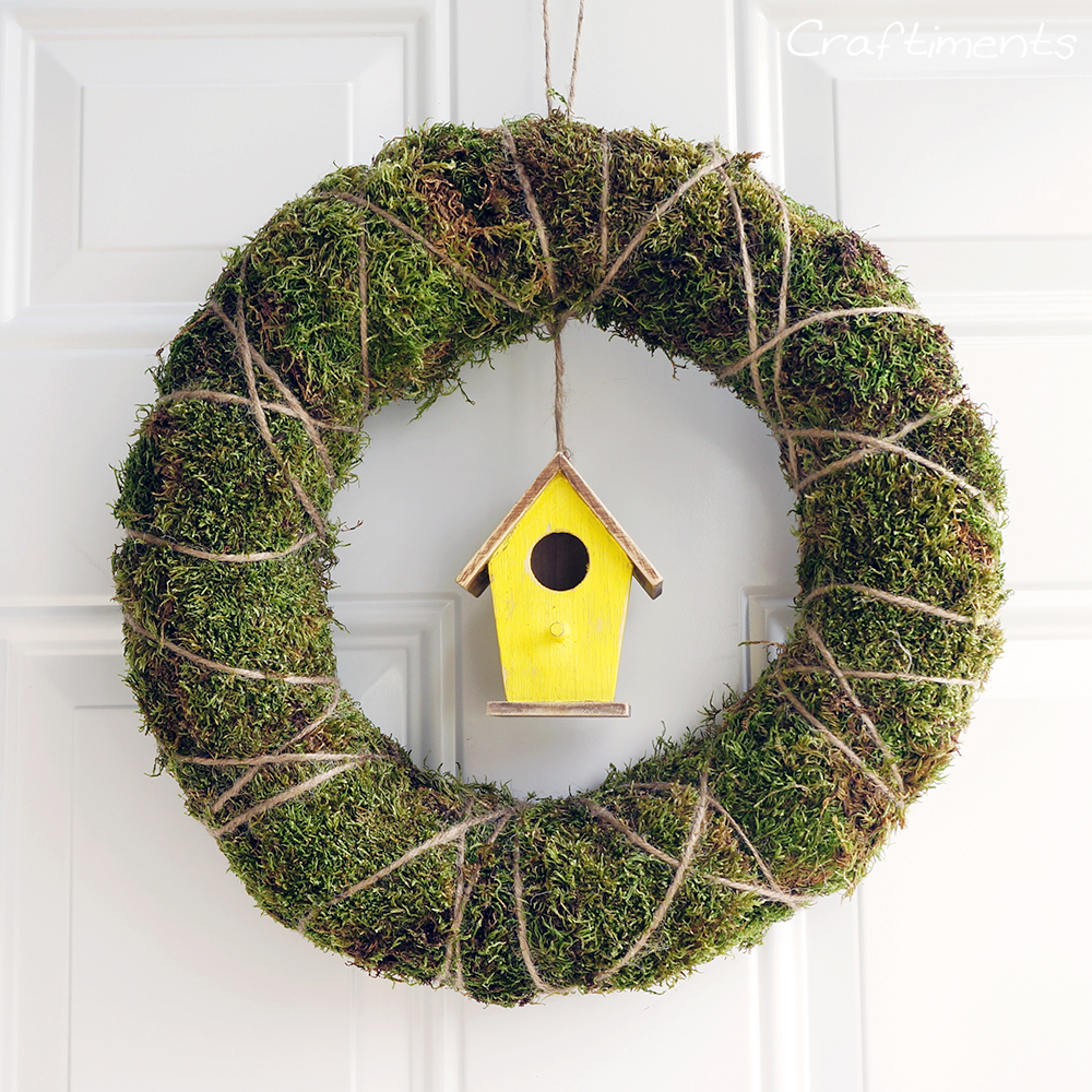 Frugal and easy to assemble moss and twine wreath with birdhouse suspended inside.
