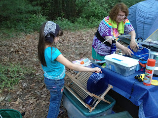 girl putting dishes in drying rack while camping