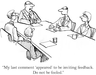 "In a cartoon, the boss at the head of the board room table tells others not to be fooled by his ""appearing"" to be inviting feedback."