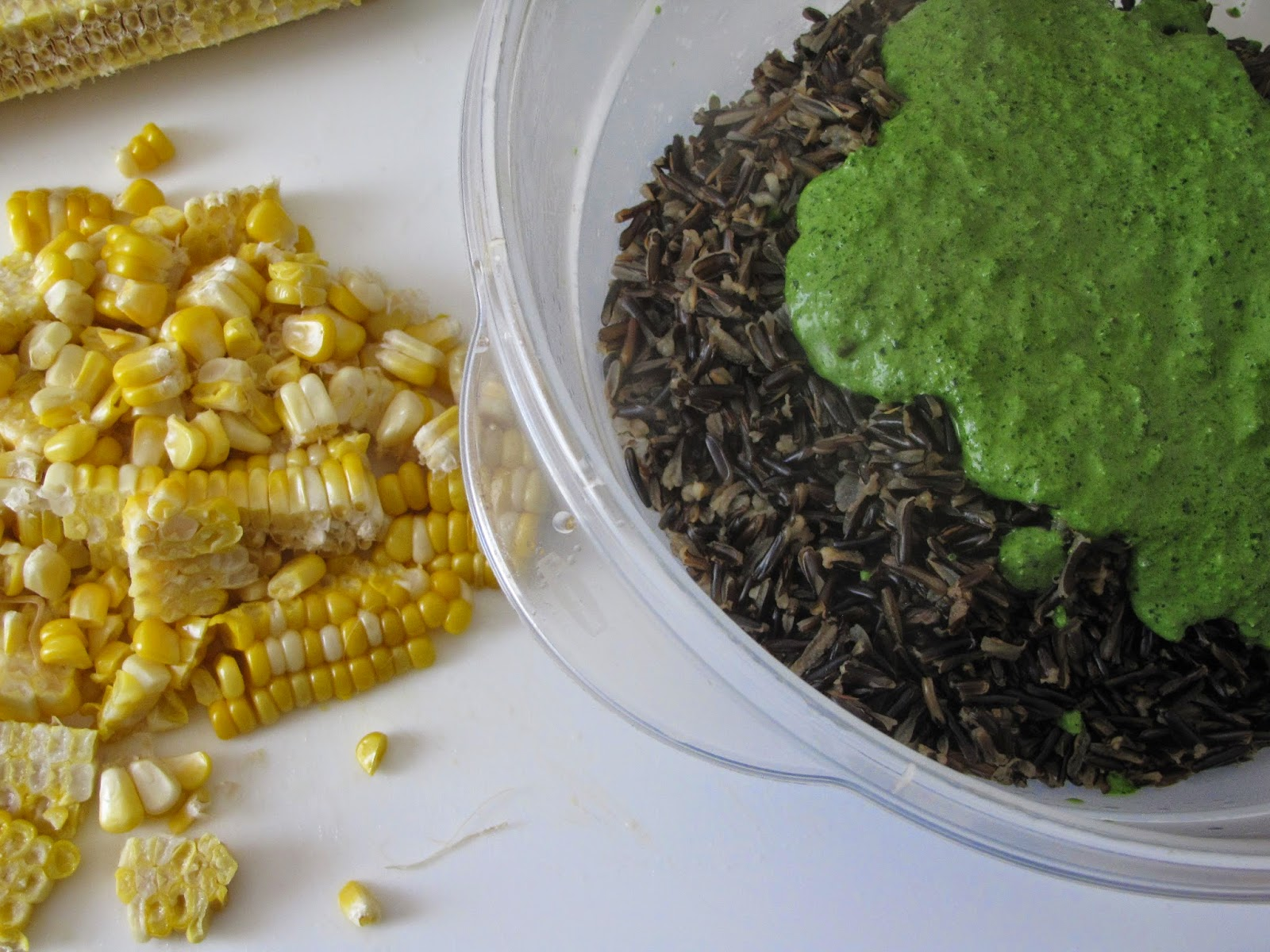 Pesto splashed on wild rice in bowl and corn kernels on a white board