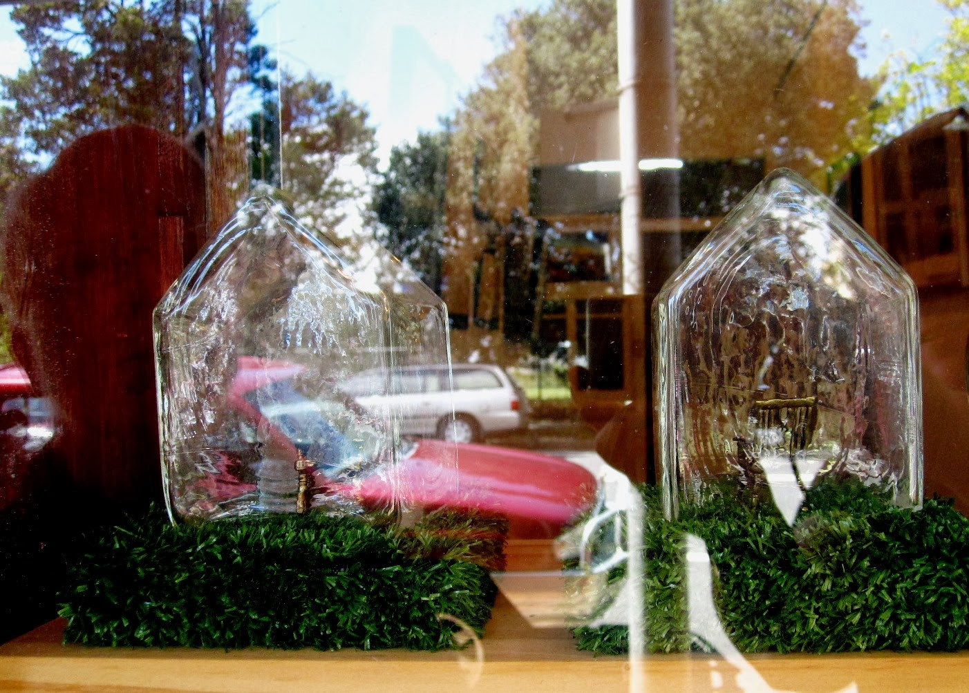 Handmade glass houses with miniature chairs inside, sitting on fake grass