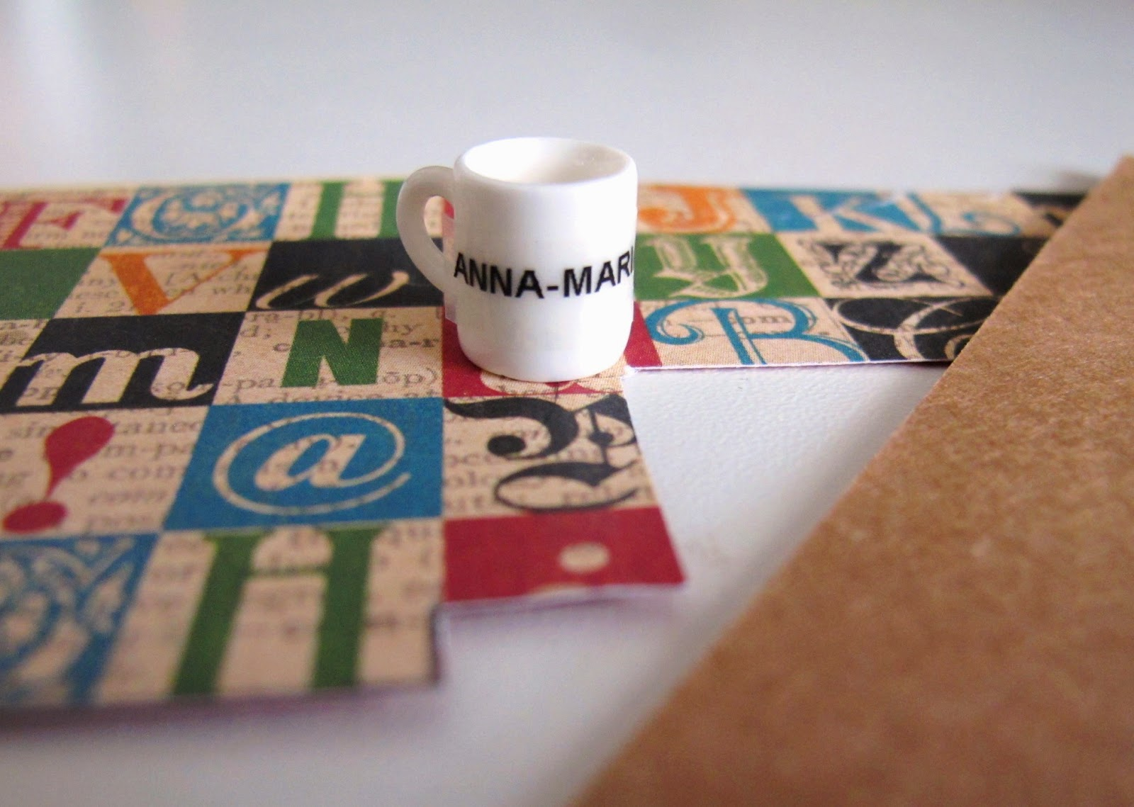 A piece of scrapbooking paper printed with squares containing typography. On it is a dolls' house miniature mug, and next to it is a piece of brown cardboard.
