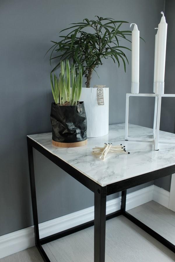 oohh krukor, oohh pappkrukor, vit kruka av papp, svart kruka av papp, marmor, diy marmorbord, diy sidobord, vårlökar, grön växt, kubus look alike, kubus ljusstake, tändstickor, inredning, inspriation, gråa väggar, måla grått, stearinljus, ljus, detaljer på bord, ikea sidobord, plastfilm, vit ljusstake netto, netto inredning