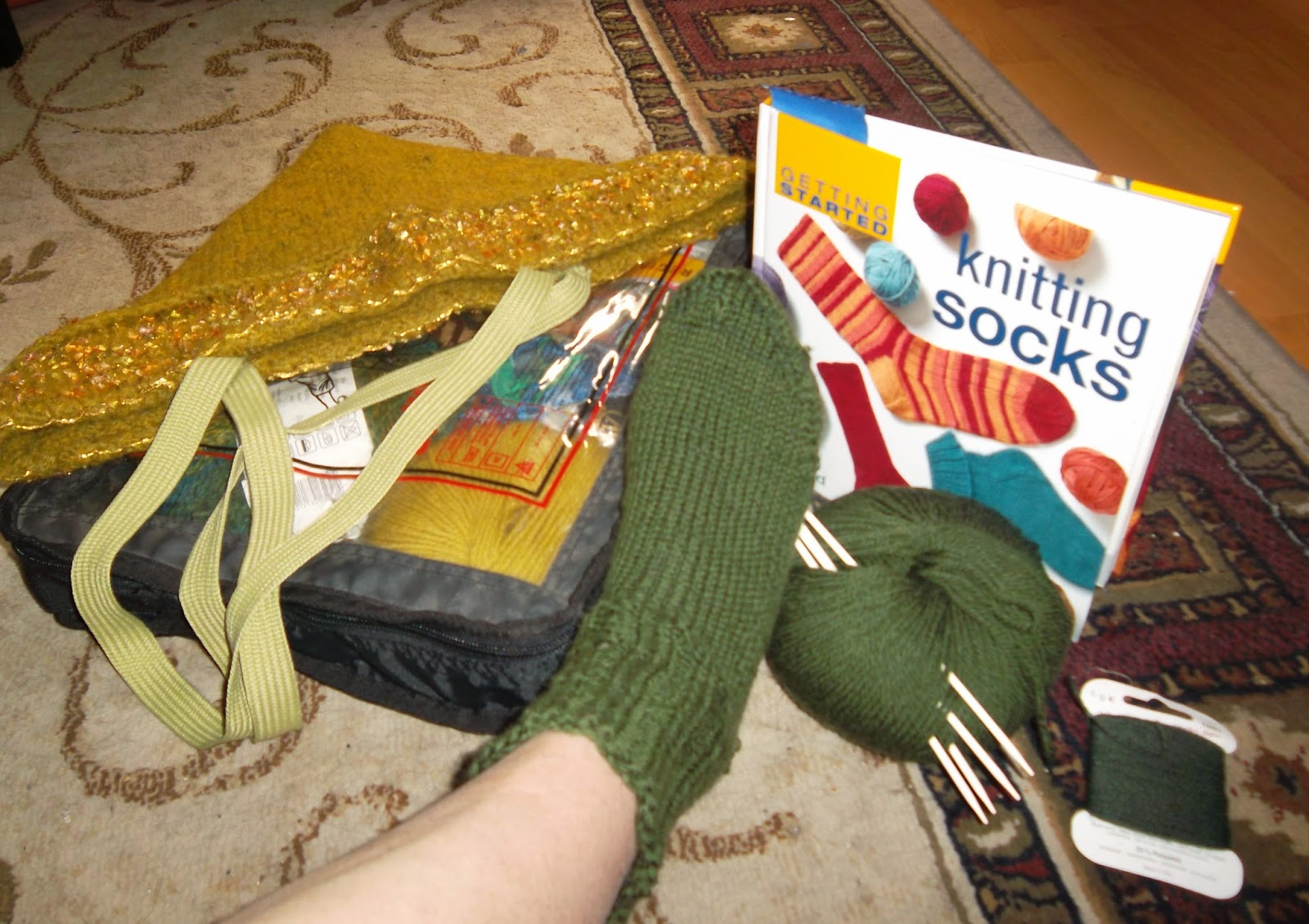 Right foot wearing a hand-knit sock in forest green. Arranged with it are a ball of yarn with knitting needles, nylon thread, a book by Ann Budd: Getting Started Knitting Socks, and a carrying case with clear cover through which more yarn is visible.