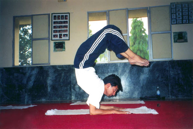 Yoga master Rajendra Pandey demonstrating Vrschikasana or scorpion pose at Yog Niketan Rishikesh