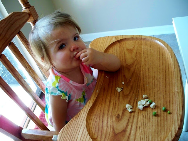 Eating peas and chicken in the highchair