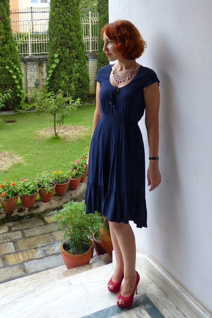 Nave blue dress with asymmetrical hem, statement necklace, high heel shoes