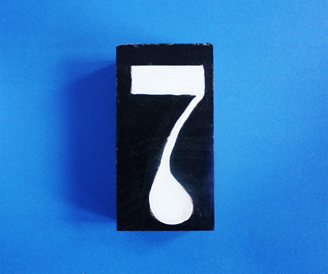 photo of number seven painted on wood on blue background