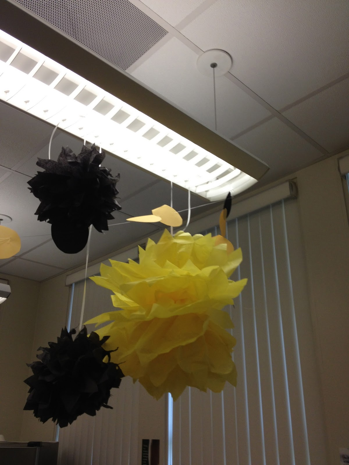 yellow and black tissue paper pom poms