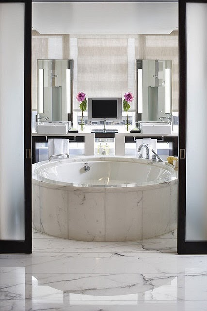 modern white master bathroom with round bath tub in marble