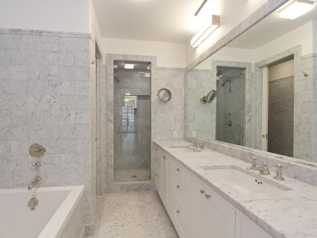 Master bathroom with Carara marble counter top and walls, deep step in tub and white cabinets