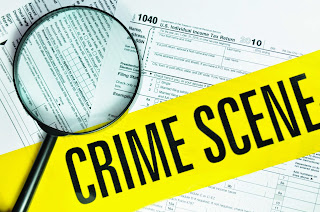 Insurance fraud file featuring IRS statement, handcufffs and a magnifying glass