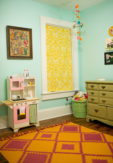 Bright and fun, colorful little girl's room on a budget. Gallery wall, DIY chandelier and roman shades, play kitchen, bright-colored rug from Serena and Lily