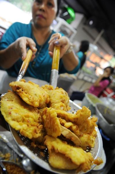 SEORANG wanita menggoreng tauhu di sebuah kantin di Jakarta semalam.