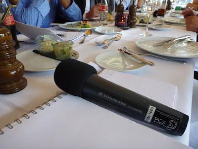 Ein Sendemikro liegt auf dem Esstisch eines Restaurants, zwei Stenoblöcke daneben