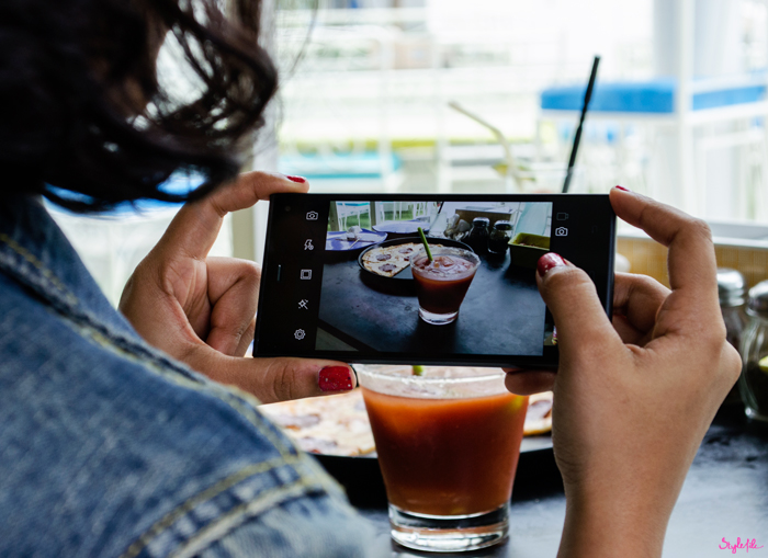 Dayle Pereira of the blog Style File takes a picture of pepperoni pizza and a bloody mary for her Instagram profile on the camera of her Phicomm Passion 660 smartphone at brunch