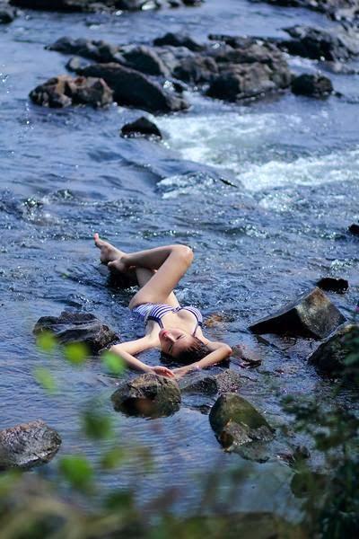 Girl Bikini Bao Truc daring semi nude beside a stream