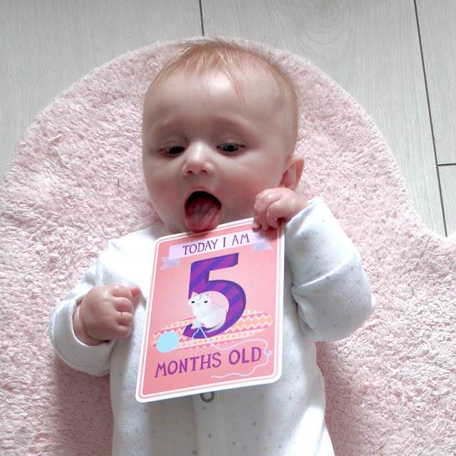 baby holding five month old milestone card