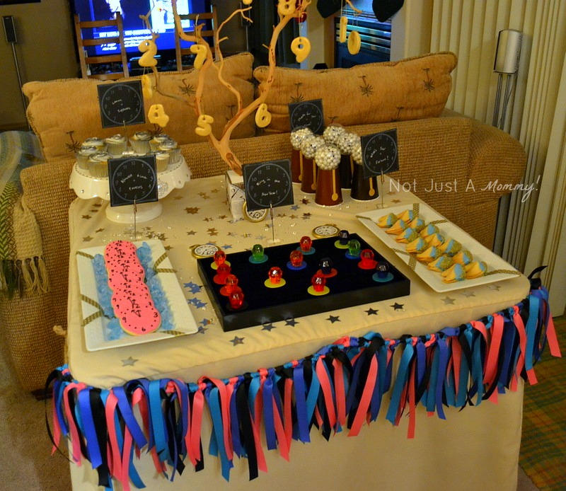 colorful and glittery new year's eve party dessert table