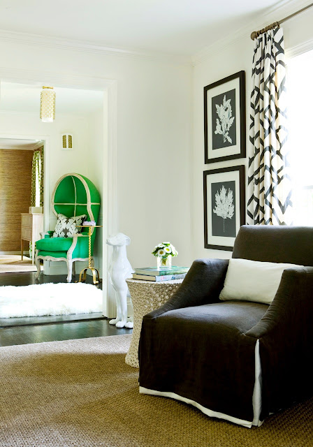 View from den to living room with a green dome chair, graphic black and white curtains, a dark brown armchair and a a woven sea grass sisal rug