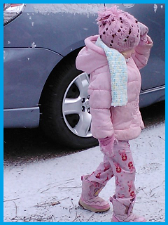 My daughter in a coat over her pink pajamas, boots, gloves, and a hat.  Searching for better snow.
