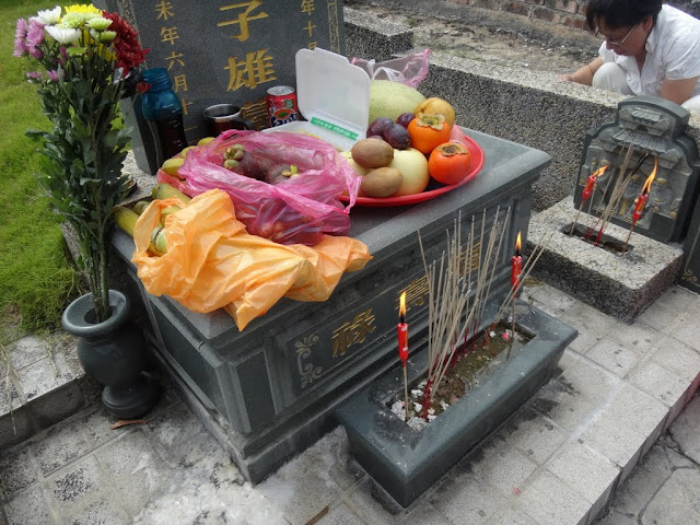 Offering some vegetarian food  and fruits besides,  joss paper and joss sticks to ancestors and loved ones after cleaning the tombs at Chinese cemetery in Malaysia