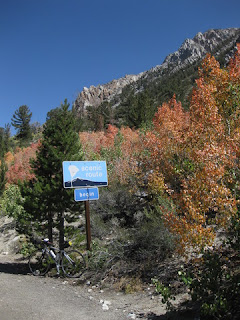 Bicycle, orange aspens, and rocky peaks with sign Begin Scenic Route near Lake Sabrina, Eastern Sierras, California