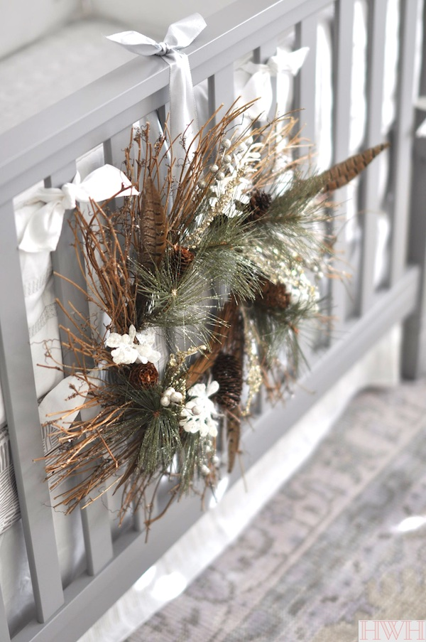 Pretty holiday wreath hung from crib in nursery | Honey We're Home