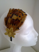 Tocado de plumas con flor de piel natural, sobre siadema forrada de raso.