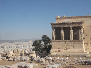The Porch of the Caryatids on the Erechtheum with the view of Athens from the top of the Acropolis.