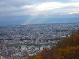 View of Sapporo city from Mount Moiwa with Autumn leaved trees in foreground and beams of sunlight and 100th memorial tower in background