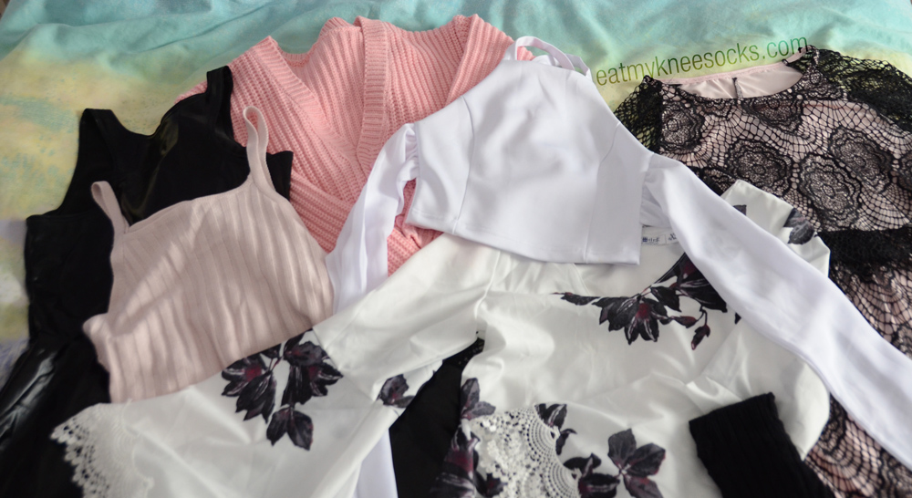 All the items I got from my third JollyChic fashion haul, including a wet-look skater dress, pink crop top, lace floral shift dress, pink oversized cardigan, white tie-back crop top, lace tights, and lace crop top/skirt set.