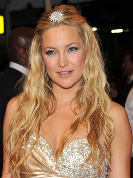 A glowing Kate Hudson shows off her golden waves with a half-up hairstyle and sparkling accessory.