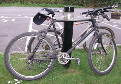 2 Mountain bikes leaning against a post