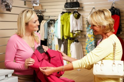 Woman buying clothing in store from clerk