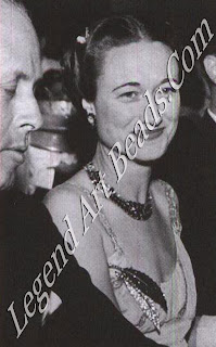 Duchess of Windsor at the Bat des Petits Lits Blanes at Cannes (1938), wearing a necklace and earrings of faceted rubies and diamonds and a large clip depicting a double holly leaf;