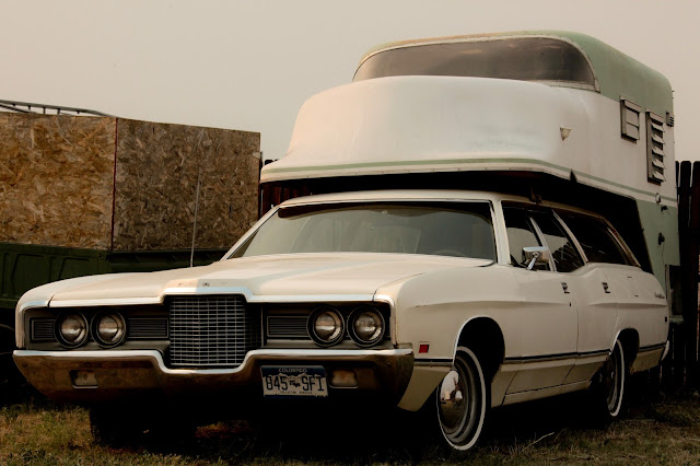 A 1970's era Ford station wagon with a crazy looking camper shell on top of it.