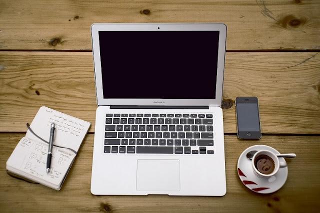 ordenador sobre mesa con cafe