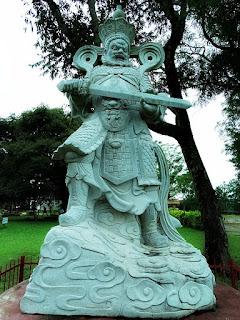 Estátua de guerreiro de pedra, com espada na mão.