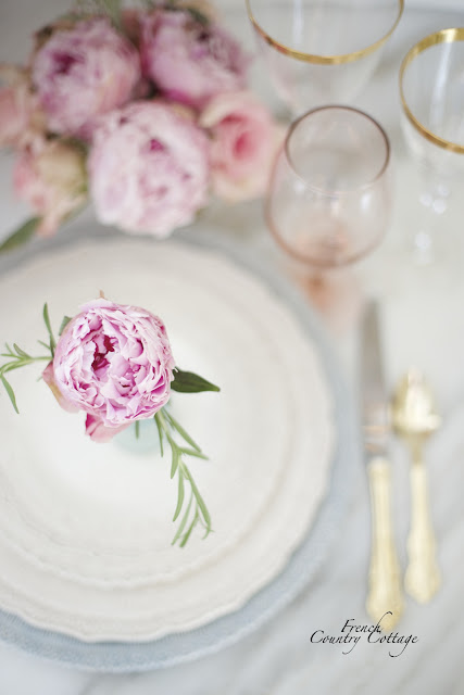 Peonies and rosemary place setting bouquet on plates with gold flatware