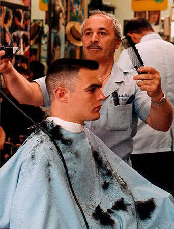 A man getting a flat top haircut at the barbershop