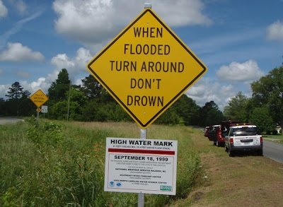 Funny road sign - When Flooded Turn Arounbd Don't Drown