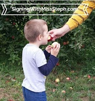 4 year old tastes an apple held out to him