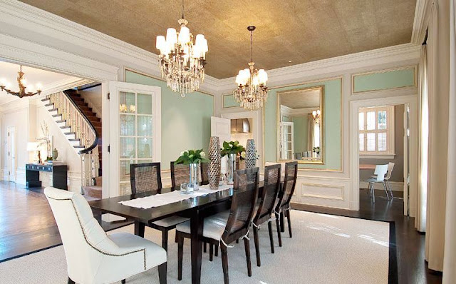 formal dining room with mint paneled walls, gold trimmed molding, gold ceiling, two chandeliers and a long dark wood table with an arm chair at the head.