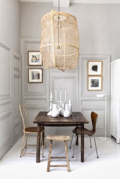 Dining room with paneled walls in a tiny French apartment with mismatched Arne Jacobsen Series 7 chairs, reclaimed wood table and an oversized pendant light