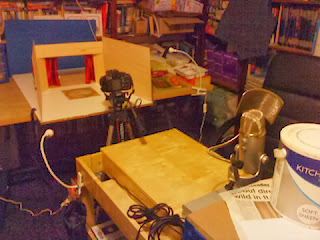 Photograph of animation studio workshop: workbench, laptop desk with microphone, camera on tripod, theatre set on shooting trestle table.