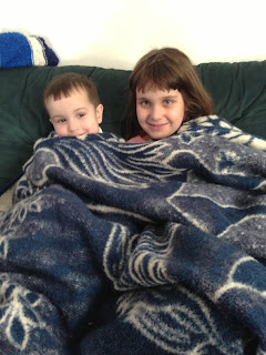 Two young kids snuggling under a warm blanket