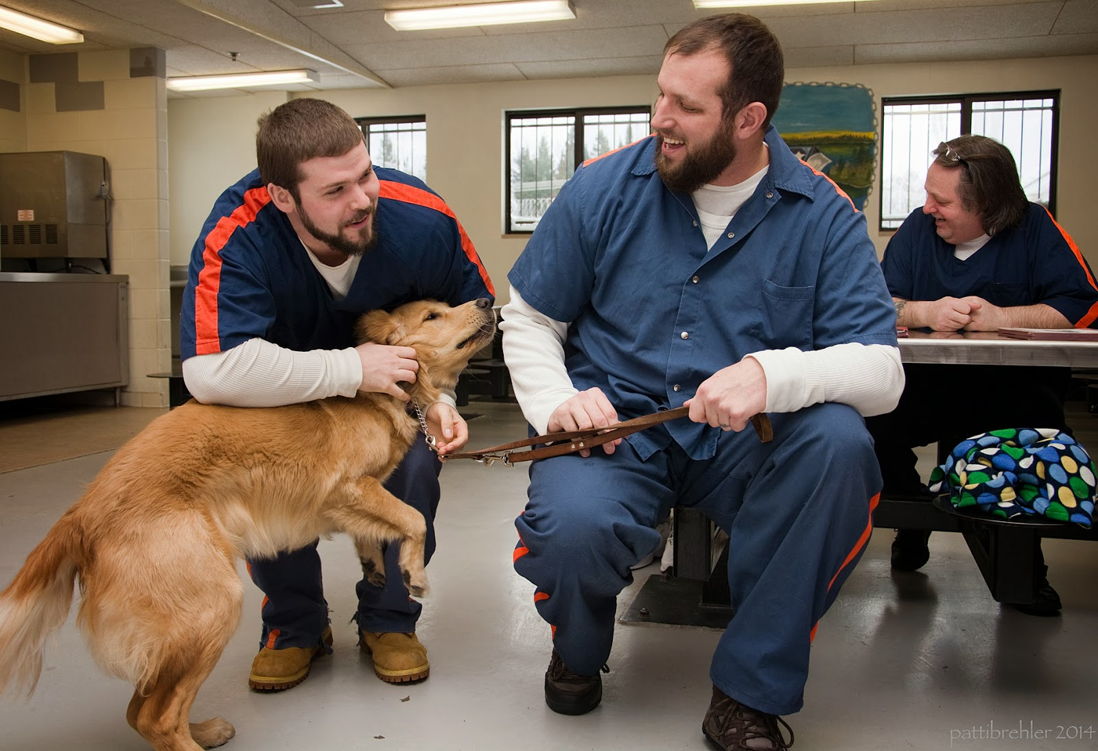 An older golden retriever puppy is being hugged by a young man on the left and his leash is held by a tall  young man sitting down on the right. The men are looking at each other and smilling. They are both wearing blue shirts and pants. The one on the left has oranges stripes on the shoulders. There is a man in the backgroun on the right sitting at a metal table .