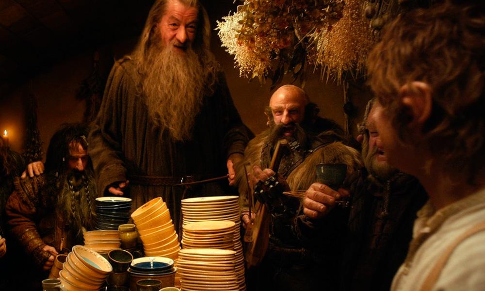 Cena do filme O Hobbit – Uma Jornada Inesperada onde gandalf esá com dois anões em frente a uma mesa cheia de louças variadas