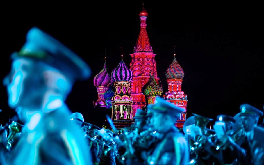 "St. Basil Cathedral is lit using show lights as Serbian Nish military band members perform during the rehearsal of ""Spasskaya Tower"" International Military Orchestra Music Festival at the Red Square in Moscow, Russia, Friday, Aug. 29, 2014."